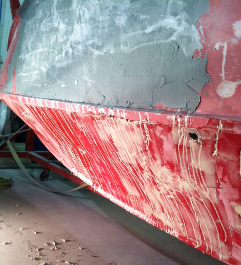 The many cracks in the hull were ground out and filled in preparation for applying new fiberglass and gel over it.