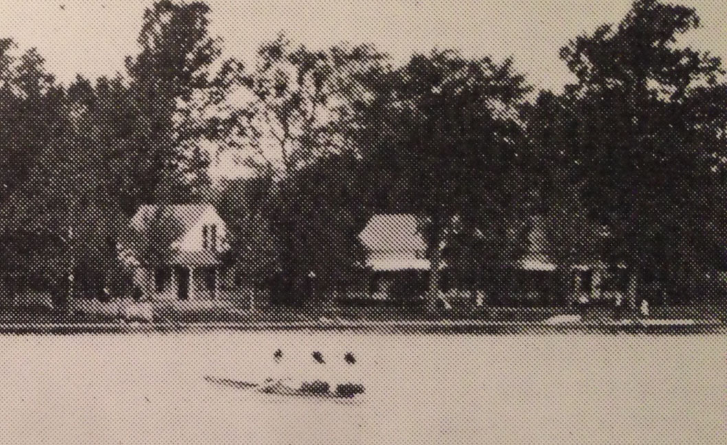 The view is partially obscured by trees. The 3 cottages as they appeared during that era.