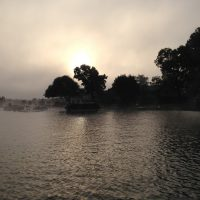 Sun rising behind Eagle Point, shining through fog on the morning of the boat count, July 4th