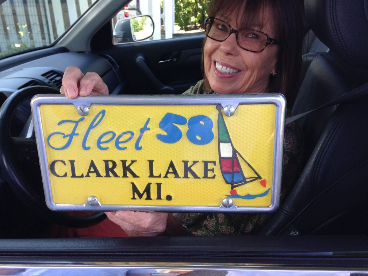 Peggy Collins is holding a valuable piece of Clark Lake memorabilia, on loan from the Beach Bar treasure chest of such items.